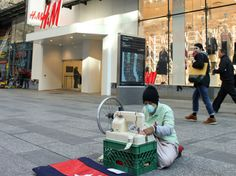 Khmer-American Artist Sews Dollar Bills for 8 Hours Outside NYC H&M to Protest Treatment of Cambodian Garment Workers | Ecouterre