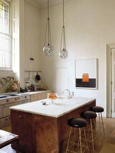 Ruime keuken met keukeneiland van hout met een werkblad van marmer.
