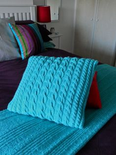Cyan colour yarn, bed trow and coordinated cable pattern cushion, knitted by me!