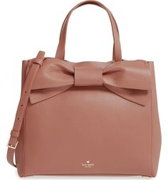 An oversized bow adds vintage cosmopolitan charm to this lightly structured satchel in buttery-soft pebbled leather by Kate Spade.