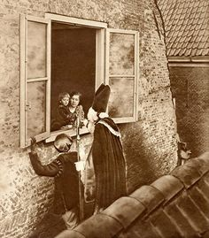 Sinterklaas en Zwarte Piet op een dak voor het open raam op bezoek bij een moeder en kind. Nederland, 1925.  English: Saint Nicholas on a roof, visiting mother and child. The Netherlands, 1925.