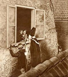 Sinterklaas en zwarte Piet op een dak voor het open raam op bezoek bij een moeder en kind. Nederland, 1925. English: Saint Nicholas on a roof, visiting mother and child. The Netherlands, 1925.