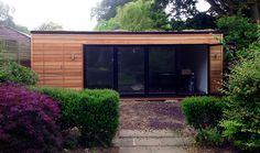This large chill out room at the end of the garden also houses a discreet shed area. Designed and built by London Garden Rooms
