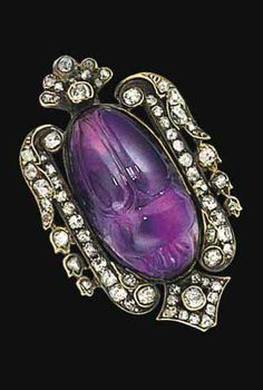 A late 19th century amethyst and diamond scarab brooch. The central amethyst carved as a scarab within an old brilliant and rose-cut diamond stylised foliate frame, with diamond-set lozenge-shaped panels above and below, mounted in silver and gold, circa 1890. #Victorian #scarab #brooch