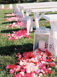 out door weddin: Rustic looking benches with glass lanterns and candles inside with the rose pedals for a more rustic spin on it