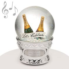 "Musical Water Globe - Champagne Bucket - What occasion are you celebrating? This musical water globe makes a wonderful gift! Perfect for any special celebration such as an anniversary or ""big"" birthday, it has two champagne bottles along with the message ""Let's Celebrate"". Fittingly, it plays the song ""Shall We Dance"" (Rogers & Hammerstein)."
