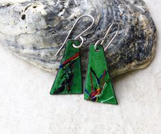Painterly enameled copper earrings, green with multi color melted swirls, many colors mixed together for a fun effect. These were torch fired with vitreous glass enamel and while heated the swirls …