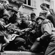Cherbourg. June 28, 1944. American soldiers and French civilians celebrating the liberation of the city in front of Cherbourg's city hall.