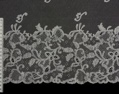 Bucks point bobbin lace bonnet veil. 113cm x 56cm. Purchased by the North Downs Lacemakers from the estate of the late Vicky Bulmer and given to The Guild in her memory. Catalogue: VBU.6.1997