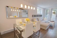 Dining room - model condo - basement unit with alot of natural light - colours are yellows and white and gray.  Le Desaulniers condos in Montreal