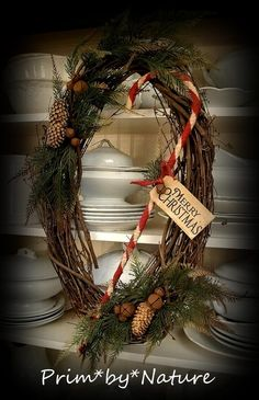 This wreath boasts a gorgeous combination of twigs, greens, rusty bells