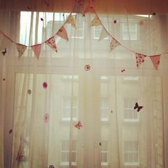 Kids bedroom curtains I made using a plain net curtain and a hot glue gun with scrap booking bows/flowers/butterfly and bunting :)