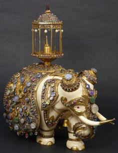"EXQUISITE ASIAN IVORY VERMEIL JEWELED ELEPHANT Most exceptional Southeast Asian ivory elephant encrusted in vermeil silver ceremonial dress jeweled throughout with sapphire, opal, ruby, emerald, citrine and pink sapphire. Gold toenails and gold vermeil jeweled ankle bands. Has stuppa chair to top of back. Measures 9 1/2"" height x 9 1/2"" length x 4 3/4"" depth (24.1cm x 24.1cm x 12.1cm). Total weight of approx. 1291dwt / 2008 grams."