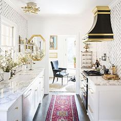 Perfect elegant small kitchen. No upper cabinets keep it feeling airy and let the elegant paper and range hood stand out.