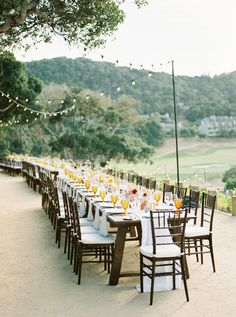 Long farm table reception for wedding at Carmel Valley Ranch. Vineyard wedding with yellow glasses and long soft white table runners. Bistro lights above long wooden tables. #CarmelWedding #FarmTables #FallWedding