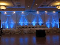 Love the pop of color that the blue lighting adds to this wedding head table backdrop!