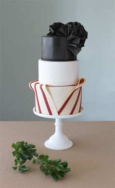 Chloe by Charm City Cakes - Unique and eye-catching three tiered cake is stunning in it's deceiving simplicity. The third tier has a red and white striped wrapped effect, the second tier is a pretty and simple white, with an eye-catching black top tier and ruffled black bow topper. Stunning!