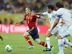 Iniesta (l) läuft mit den Ball am Fuß den Uruguayern davon. (Foto: Srdjan Suki/dpa)