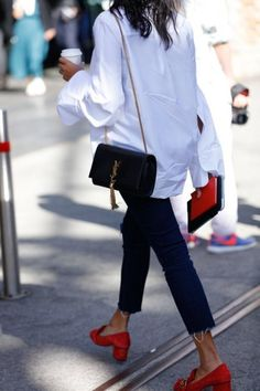 Touch of red. Blue jeans, white tee, black shoulder gbag and red shoes and clutch. Fashion trends.