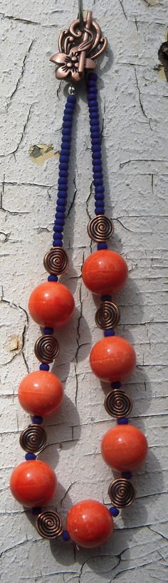 "Fun Orange Cermic Designer Beads are Hand-Crafted and Strung Along with Antiqued Brass Swirls and Midnight Blue Glass Beads. This is definitely a Perfect Combination of Tribal and Funky to Compliment Any Look for Fall!    Length is Approximately 16.5""    Antiqued Brass Toggle Clasp with Decorative Floral Design    Find me on Facebook for FREE SHIPPING PROMO CODES! http://www.facebook.com/RoyalRubyJewelry    Follow me on Twitter: RoyalRuby Jewels    Return to RoyalRuby's shop on Etsy.com…"