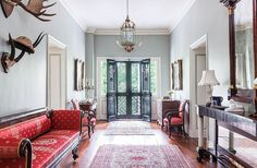 "A gorgeous wide open hallway leads to the entryway and foyer, painted a soft pale dove gray and edged in intricate, classical millwork and mouldings. Bright pops of red -- in the forms of a vintage Persian rug, matching upholstered red silk arm chairs and a stunning scroll-arm day bed -- add a perennial festive touch, as does moose antlers above. See fine-jewelry designer Elizabeth Locke's full home tour in ""A Stunning Estate with Southern Grace and Italian Romance"" over on our Style Guide!"
