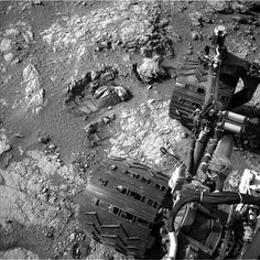 """This view of Curiosity's left-front and left-center wheels and of marks made by wheels on the ground in the """"Yellowknife Bay"""" area comes from one of six cameras used on Mars for the first time more than six months after the rover landed."""