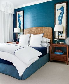 Deep, rich blue teamed with white for a chic bedroom with a hint of the romance of the sea. The white wardrobe drapes add a sense of the fluidity of waves and the rattan headboard of the colour and texture of sand.