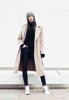 Street style look preto, sobretudo bege, tênis branco e gorro cinza.