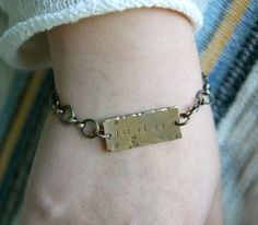 """This bracelet is an invitation to set down what no longer serves you.  This bracelet includes a raw brass rectangle hand stamped with the words  """"let it go"""" that is antiqued by hand and 1.25 inches in length. The  hammered texture and hand-stamped letters are done by hand and will vary  with each handmade bracelet. The chain is plated antique brass. The  bracelet comes in three sizes: adjustable to 7, 8, or 9 inches. The last  photo shows several bracelets and necklaces from the 1993…"""