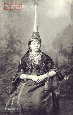 The traditional vertigious tantour hat of a married Druze (a monotheistic religious community) woman of Lebanon (sadly not an example of the popular trend to replicate the landscape of late 19th century Sheffield at parties in Damascus...!!). The tantour, similar to the hennin (worn in the late Middle Ages by European women of the nobility), was popular in the Levant during the nineteenth century, but seldom seen after 1850 - making this card somewhat of a rarity. The height of the tantour…