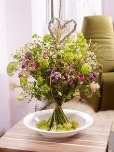 """Rose kann jeder... Es muss nicht immer die Königin der Blumen in der Symbolfarbe Rot an Valentin sein. Dieser Motivstrauß trifft mit seiner Natürlichkeit mitten ins Herz. Der liebevolle Strauß drückt mit seinem eingearbeiten Deko-Herz ganz Besonderes aus: """"Ich freue mich auf den Frühling an Deiner Seite"""". Strauß designed by FDF Foto: Blumenbüro & FDF, J. Manegold"""