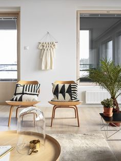 Two matching wood chairs with black and white pillows, hanging wall art, and indoor plant