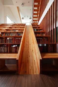 Architect Moon Hoon designed the Panorama House in South Korea, which features a multi-functional library. A wooden slide (used by the adults in the home, too!) is flanked by stair step bookcases.