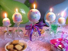 Spherical candles placed on over-turned wine glasses of varying sizes.  Just add a little ribbon and you have a centerpiece that offers warm lighting.