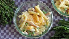 Nudelsalat mit Schinken, Erbsen und Orangen in einer kleinen Glasschüssel
