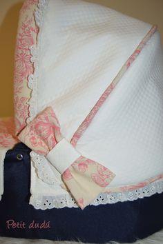 Le tela con un estampado Toule de Jouy en tonos rosas se ha combinado con un piqué marfil labrado en rombos. Para la decoración de la capota y el saco de capazo he usado un volantito bordado, y en el capazo he colocado un pasacintas con un lazo en los mismos tonos rosados.