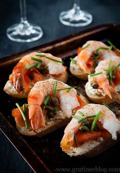Crostini with Prawn, Smoked Salmon, Boursin Cheese, Caper and Chives   Toast baguette slices until lightly golden. Allow to cool for a few minutes before spreading liberally with the cheese. Press slices of red onion into the cheese and top with smoked salmon and prawn. Garnish with capers and chopped chives. Sprinkle with salt and pepper and serve immediately.   From: gratineeblog.com