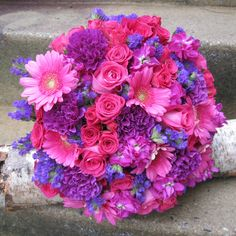 A round hand tied wedding bouquet created with hot pink standard roses with bling, purple mini carnations, hot pink mini gerberas daisies with bling, hot pink spray roses, purple carnations, statice, and magenta stock. #blossomandbasketboutique
