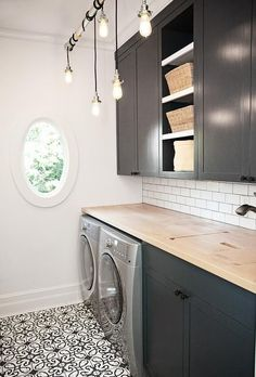 Gillian Pinchin - Black and white laundry room features industrial bulb pendants hung from a tension rod over black and white cement floor tiles and in front of black cabinets flanking open shelves.