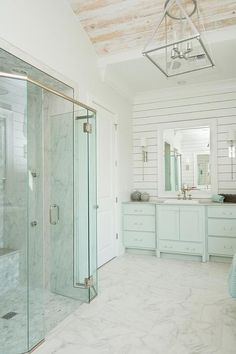 Turquoise bathroom features a turquoise blue washstand adorned with lucite pulls topped with gray marble fitted with an overmount white porcelain sink placed under a large white beveled mirror lining a shiplap wall illuminated by long nickel wall sconces.