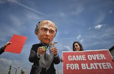 A man wearing a mask depicting FIFA President Sepp Blatter holding Swiss Francs is seen during a protest held in front of the Hallenstadium, where the 65th FIFA Congress took place in Zurich. Blatter was re-elected Friday to a fifth term amid global corruption investigations into the football governing body.