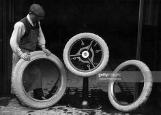 A car mechanic with a selection of Dunlop spare tyres. 1910.