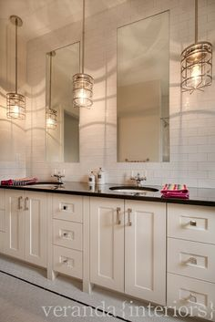 subway tile from the counter to the ceiling with tall framed mirrors inset onto the wall.