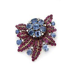 <br /> <b>Clip de corsage</b> <br /> En or jaune 14k (585), stylisé d'une fleur, le pistil serti de saphirs clairs, les feuilles de rubis nervurées d'or, l'ensemble semé de diamants taillés en brillant et de saphirs <br /> Vers 1960 <br /> Haut.: 5 cm, Poids brut: 36.01 g <br />  <br /> A sapphire, ruby, diamond, 14k yellow gold and platinum clip, circa 1960 <br /> <br />  <br />  <br />