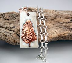 This unique, one of a kind silver chain necklace would make a fond memory as a 7th anniversary gift. Pendants for women come in many shapes and colors and this rectangular ceramic pendant has a vibrant and rich copper botanical design. It was created using the Raku method, a Japanese firing process from the 16th century; the word raku means happiness or joy. A handmade chainmaille design called the flower chain was used in the design of this white statement necklace. Sterling silver and…
