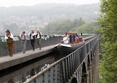 Joanne Gregory carries the London 2012 Olympic torch on a hand-drawn boat across the Pontcysyllte Aqueduct in North Wales.