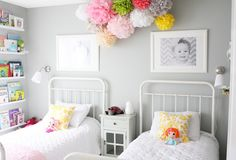 a shared girl's room.  decorating with large photos. a ceiling of tissue poms.