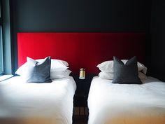 Dark decor. Dark interior style. Black bedroom. Red headboard.