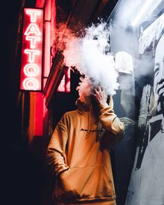 Tattoo studio neon sign in front of the shot. A guy in yellow hoodie smoking. Smoke Bomb Photography, Portrait Photography Men, Smoke Photography, Photography Poses For Men, Urban Photography, Creative Photography, Amazing Photography, Street Photography, Vape Pictures