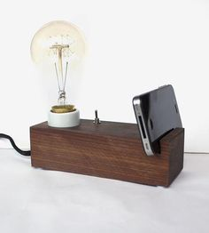 A handy helper in the kitchen or on your work table in the studio, this wood exposed bulb lamp holds your phone or tablet upright while you've got your hands full. The smoothly finished walnut block is fitted with a flip switch, a vintage-style Edison light bulb and a small groove to hold your new-fangled technology.